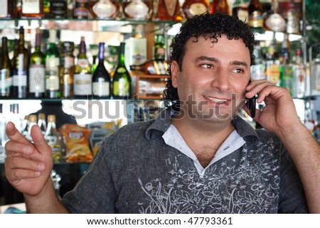 Barman talks by  Smiling man against shelves with bottles. - stock photo