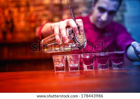 barman with cocktail shaker pouring red alcoholic drink into glasses in bar - stock photo