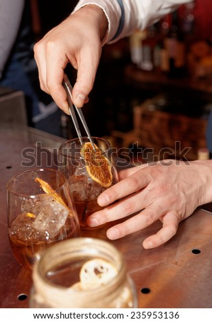 Barman works at bar counter, slightly warm toned