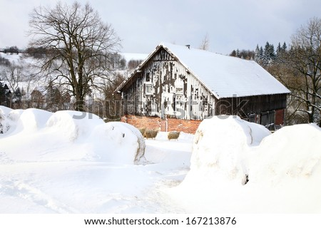 Barn and bale of straw in snow. Winter scenery on the farm.  - stock photo