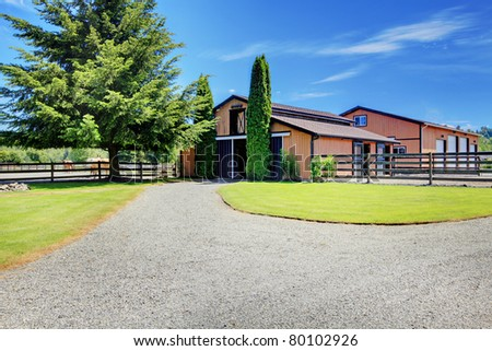 Barn and Pasture ground at the horse ranch in Washington State, USA with the wood fence and the houses in the background. - stock photo