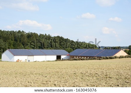 Barn of a farm with solar panels on the roof - stock photo