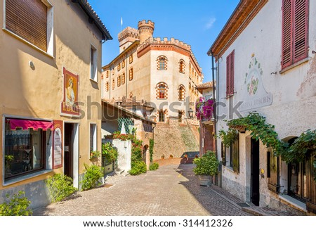 BAROLO, ITALY - AUGUST 26, 2015: Narrow street, old houses and medieval castle of Barolo - first built in X century by feudal family Falletti, restored and changed many times during the years. - stock photo