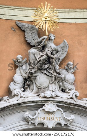 Baroque composition on the wall of the historic houses in Bratislava, Slovakia. Angels and elements on the background of red walls and golden eye - stock photo