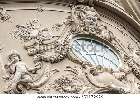 Baroque elements on one of the buildings in Bratislava, Slovakia - round window, musical and herbal elements, satires and young children - stock photo