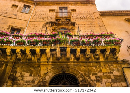 Baroque facede decorated with flowers in Italy. Beautiful travel photo. Colorful background texture with architecture and flowers.