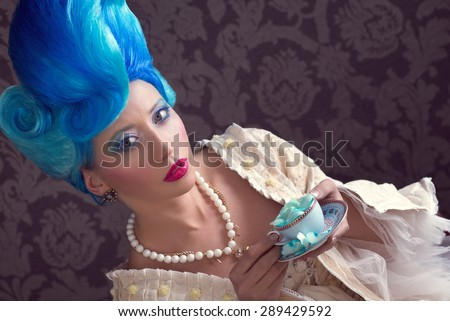 Baroque lady with blue wig and cup of rose tea - stock photo