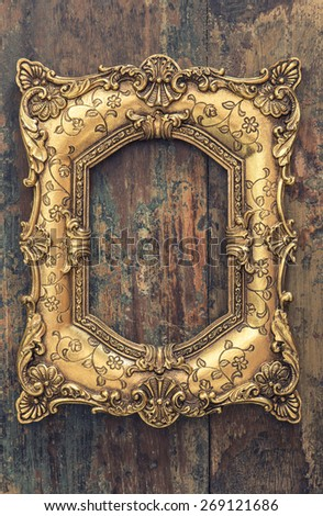 Baroque style antique golden frame on wooden background - stock photo