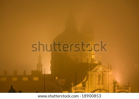 Baroque style St. Nicholas church in Prague surrounded by fog.