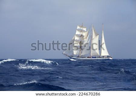 Barquentine with white sails in the calm sea - stock photo