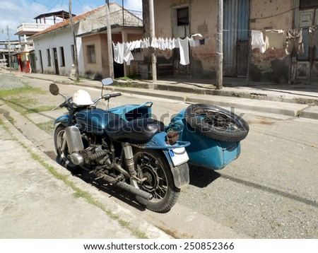 BARRACOA, CUBA - NOVEMBER 24: a vintage blue side-car is parked in a street and some clothes are hung out to dry on the other side,on november 24, 2014, in Vinales, Cuba. - stock photo
