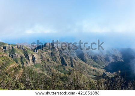 Barranco de Benchijigua on the Canary island La Gomera in clouds, which were formed above regions within trade wind. The clouds comes from the Azores and reaches the Islands in approx. 800m altitude - stock photo