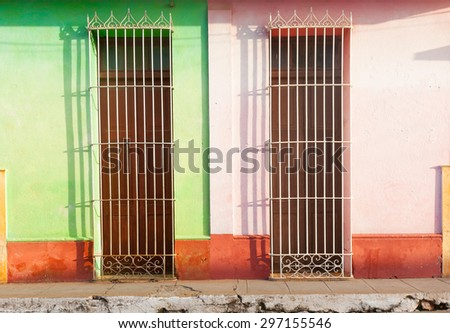Barred doors two homes differentiated by color and broken pavement in third world town  - stock photo