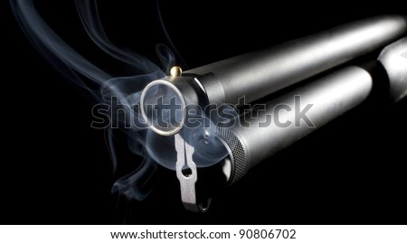 Barrel of a pump action shotgun that is surrounded by smoke - stock photo