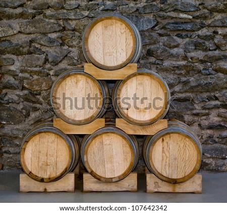 Barrels in a pyramid in a cellar - stock photo