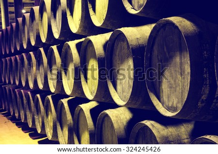 Barrels of wine or whiskey stacked in the winery - stock photo