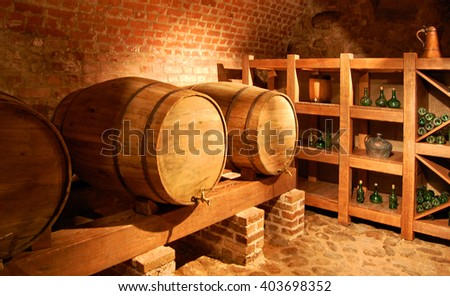 Barrels with a wine in a cellar on the brick wall background - stock photo
