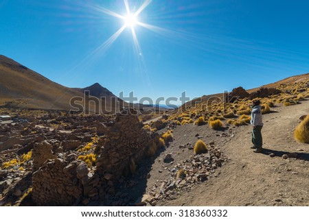 Barren mountain range on the highlands of the Andes on the way to the Uyuni Salt Flat, among the most important travel destination in Bolivia. Abandoned and ruined old colonial village in backlight. - stock photo