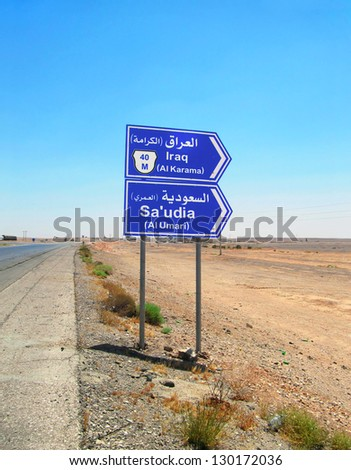 Barren view - road signpost at borderline between Jordan, Iraq and Saudi Arabia against the background of clear blue sky, The Syrian Desert, Middle East, Southwest Asia - stock photo