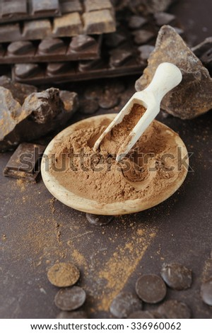 Bars, chopped and chips of chocolate with cacao powder in wooden bowl - stock photo