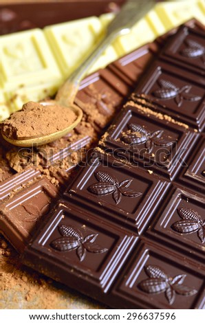 Bars of chocolate with cocoa powder. - stock photo