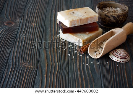 Bars of handmade soap and sea salt over natural wood background - stock photo