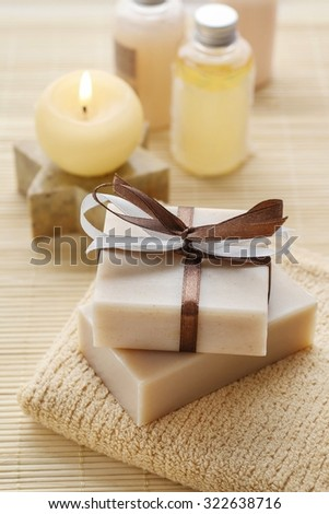 Bars of handmade soap, scented candle and bottles with liquid soap. - stock photo