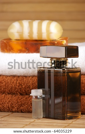 Bars of natural soap, aromatic shower gel, ampules with serum and towels on wooden background.