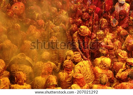 BARSANA - MAR 21: People celebrate the traditional and a ritualistic Holi at Radharani temple on March 21, 2013 in Barsana, India. Holi is the most celebrated and colorful festival in India. - stock photo