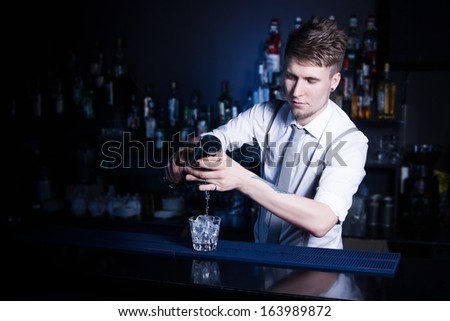 Bartender bartender is pouring a drink - stock photo