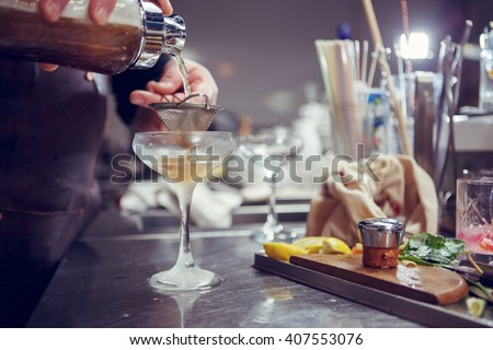 Bartender coocks cocktail behind a bar counter - stock photo