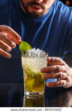 Bartender decorating mojito cocktail drink