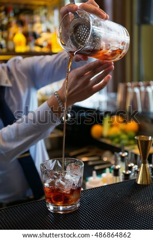 Bartender in formal dress is  pouring cocktail drink behind bar counter in luxury bar.