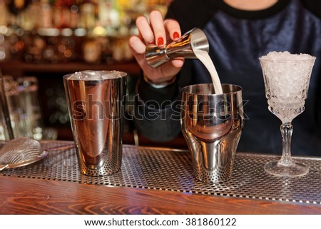 Bartender is adding milk to the metal shaker - stock photo