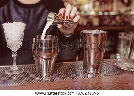 Bartender is adding milk to the metal shaker, toned - stock photo