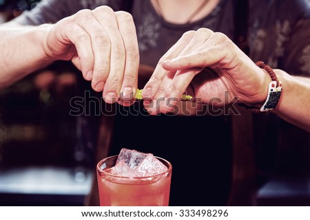 Bartender is adding zest to cocktail, toned image - stock photo
