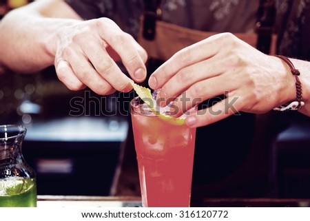 Bartender is adding zest to the cocktail, toned image - stock photo