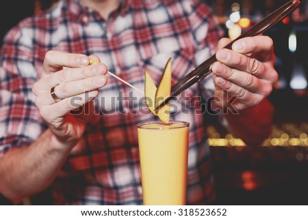 Bartender is decorating a cocktail with mango, toned image - stock photo