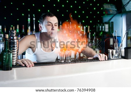 bartender is making flaming cocktail with performance - stock photo