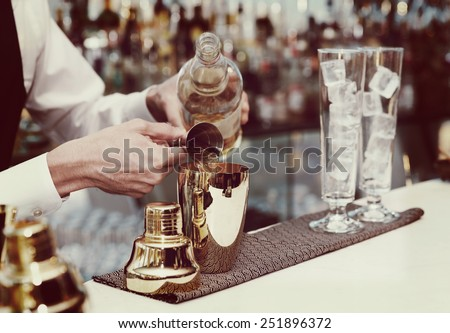 Bartender is pouring liquor in golden shaker, toned image - stock photo