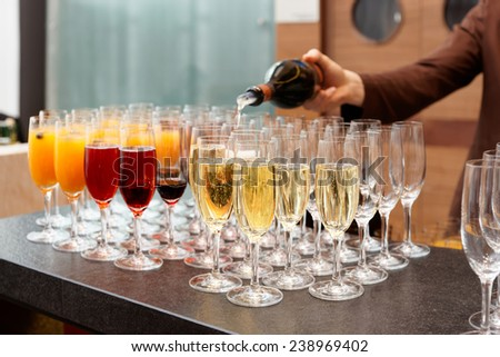 Bartender is pouring sparkling wine in glasses, making cocktails - stock photo