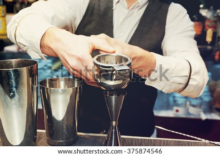 Bartender is squeezing citrus juice in jigger, toned image - stock photo