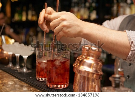Bartender is stirring cocktails on bar counter - stock photo