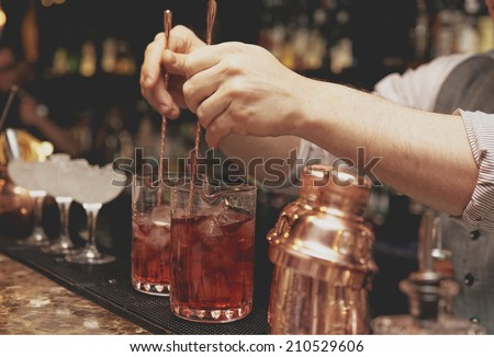 Bartender is stirring cocktails on bar counter, toned image - stock photo