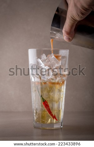 Bartender making cocktail on grey background - stock photo