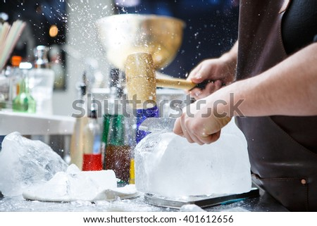 Bartender mannually crushed ice with wooden hammer and metal knife. - stock photo