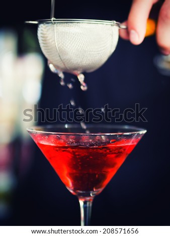Bartender pooring the cocktail into Martini glass - stock photo