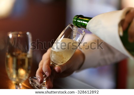 Bartender pouring champagne into glass, close-up - stock photo