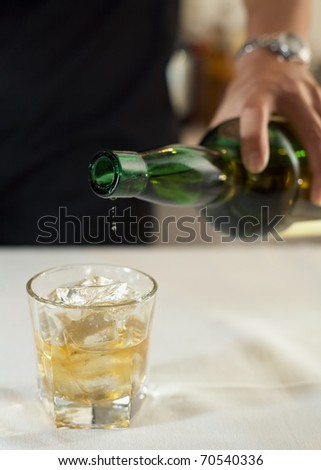 Bartender pouring glass of scotch whiskey - stock photo