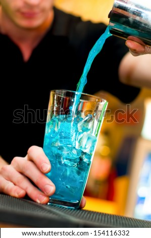 Bartender pours alcoholic drink into cocktail glass making a blue curacao  - stock photo